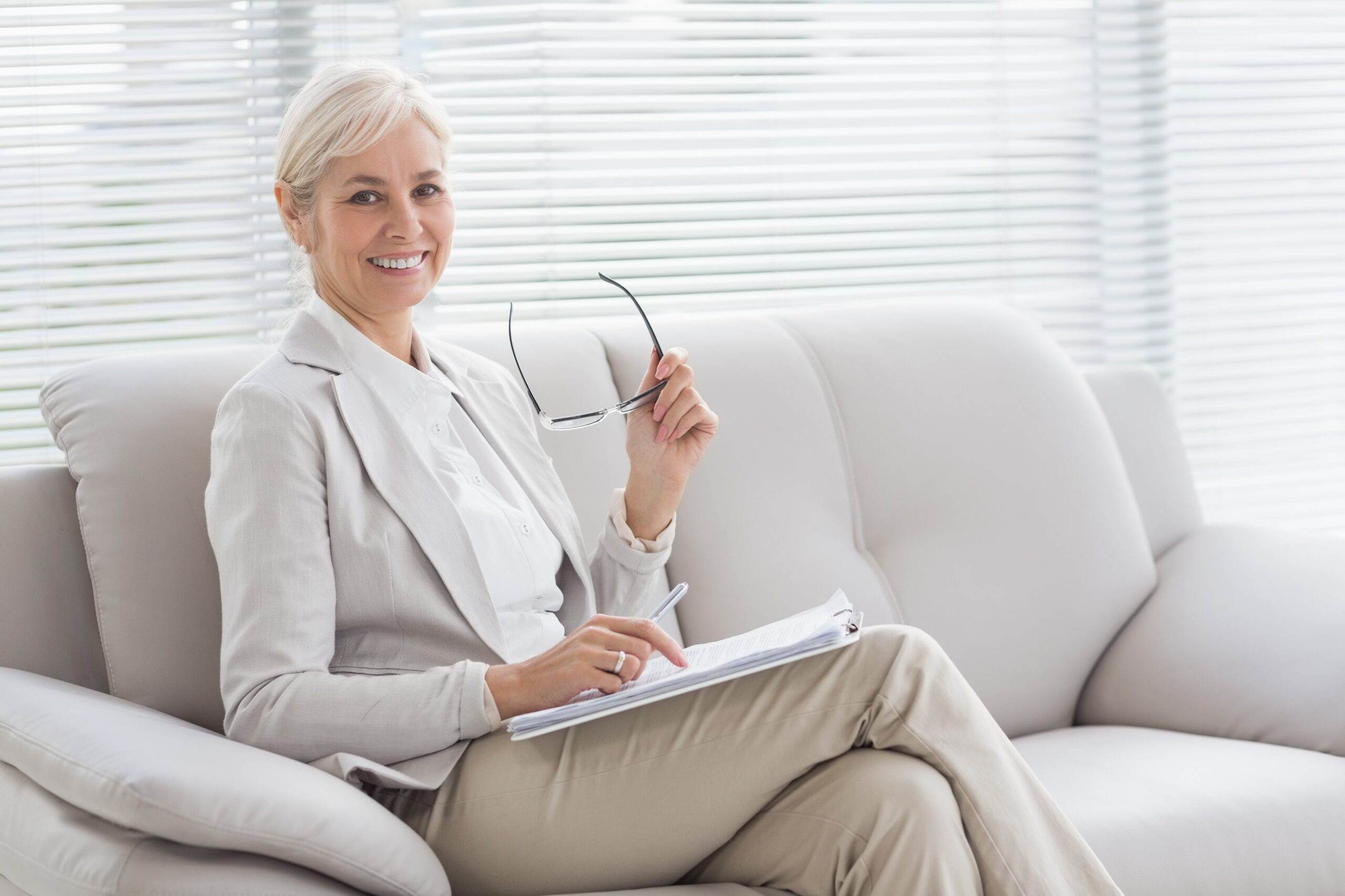 Woman with glasses in hand smiling