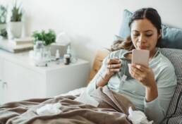 Sick woman on sofa talking to doctor on phone