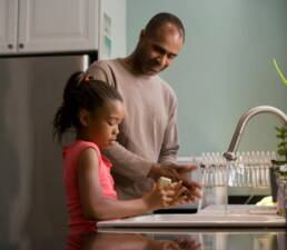 African America father washing hands with daughter